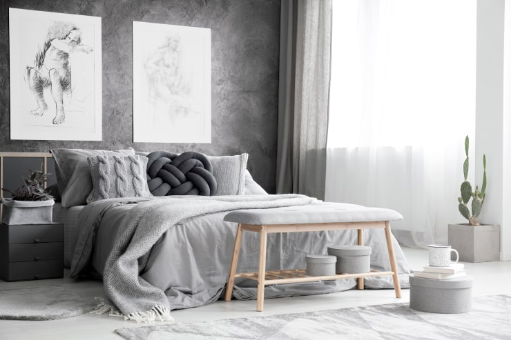 A bedroom in gray tones with a textured wall