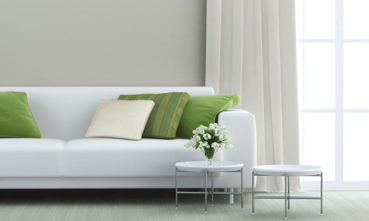 A white sofa with flowers and a window